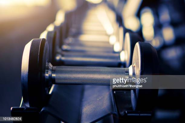 close up many metal dumbbells on rack in sport fitness center,weight training equipment concept. - mass unit of measurement stock pictures, royalty-free photos & images