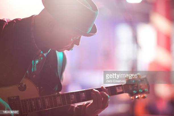 Close up mature man playing guitar on stage
