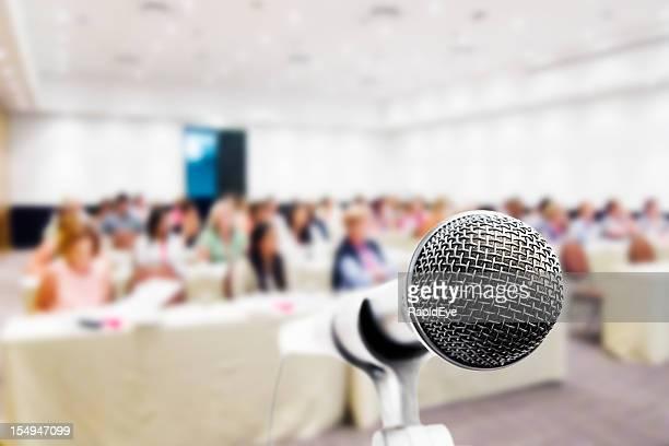 Nahaufnahme, Mikrofon, Konferenzteilnehmer im Hintergrund