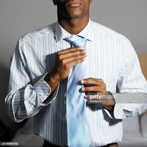close up mid section of businessman fixing his tie - adjusting necktie stock pictures, royalty-free photos & images