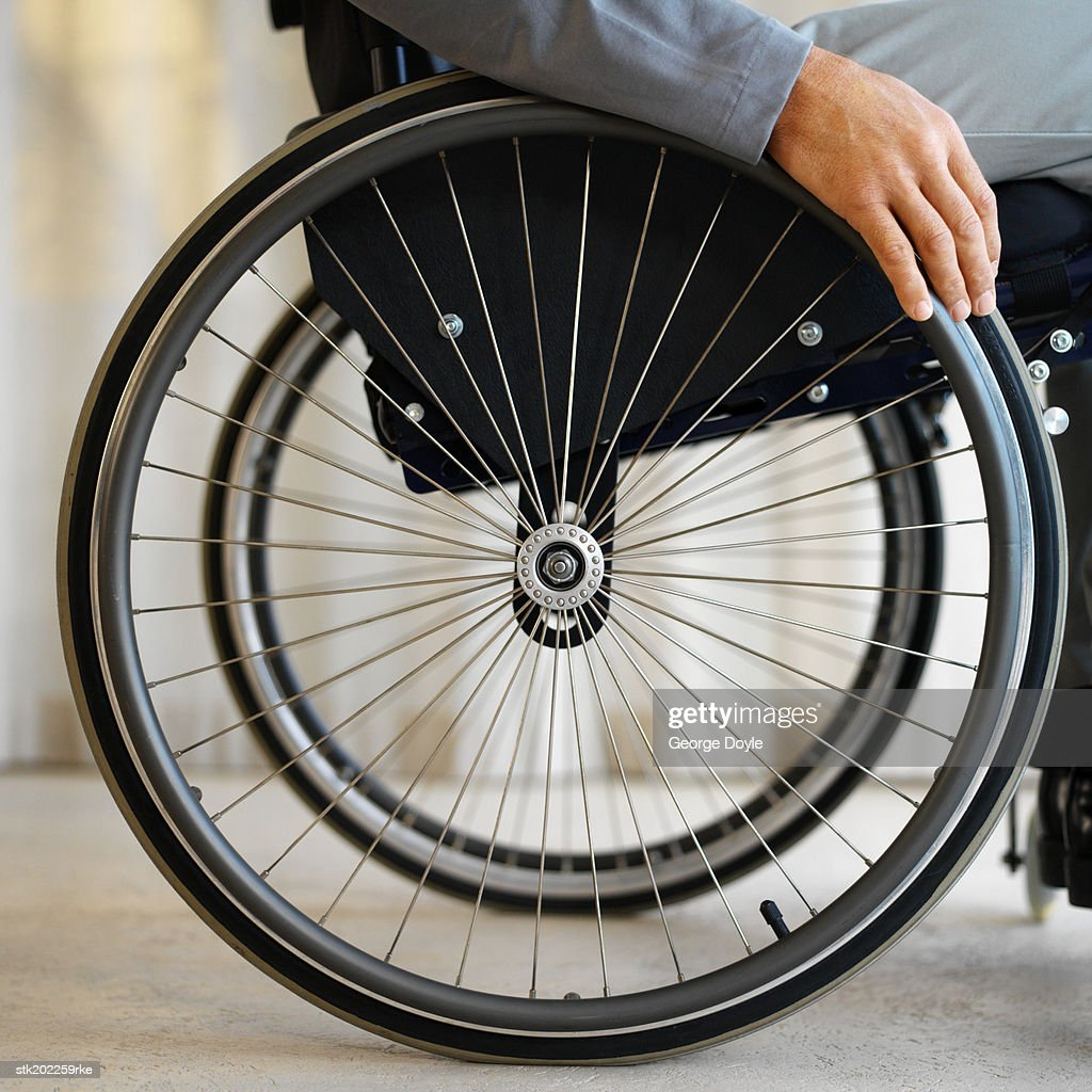 close up mid section view of a man sitting in a wheelchair : Stock Photo