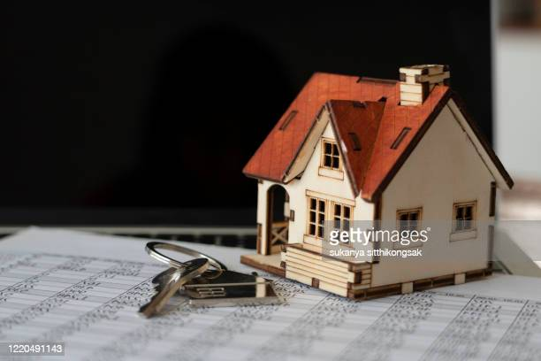 close up model houses, keys and interest rates are on a laptop.bank calculates the home loan rate. - mortgage document stock pictures, royalty-free photos & images