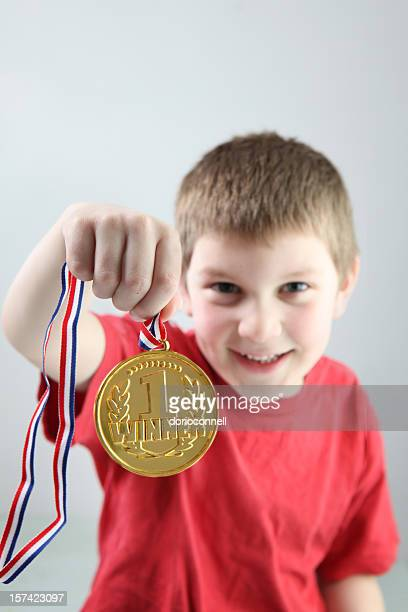 Close up of 1 winner gold medal held by smiling boy