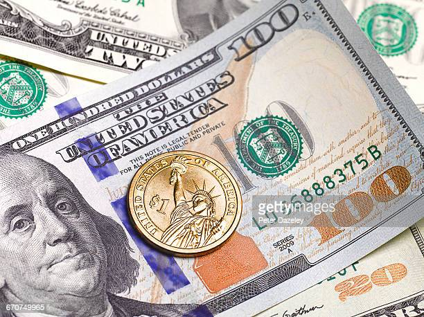 close up of $100 dollar note and 1 dollar coin - us coin stock pictures, royalty-free photos & images