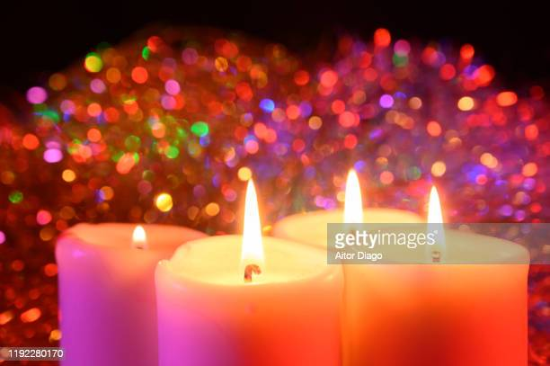 close up of 4 candles with a lit flame. christmas decoration in background. - candle of hope stock pictures, royalty-free photos & images