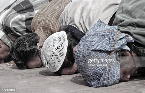 CONTENT] CLose up of 4 Muslim men praying with their faces touching the ground Jama Masjid largest mosque in Delhi India during Sabbath prayer