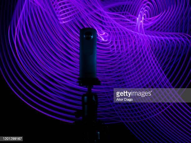 close up of a 360º camera on a tripod with a purple futuristic interconnected background - 360 fotografías e imágenes de stock