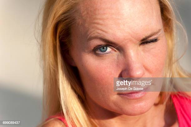Close up of a 40 year old blond woman making a face at the camera.