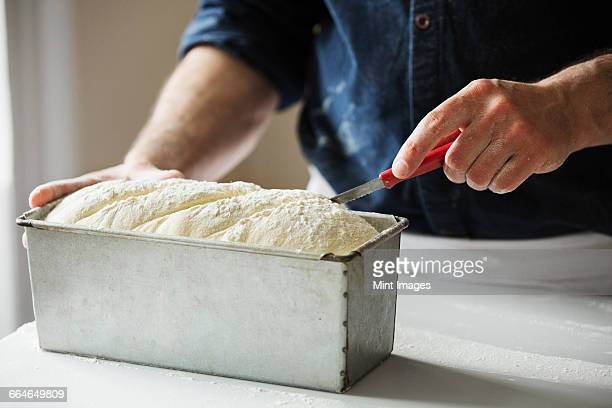 Close up of a baker cutting bread dough in a baking tin.