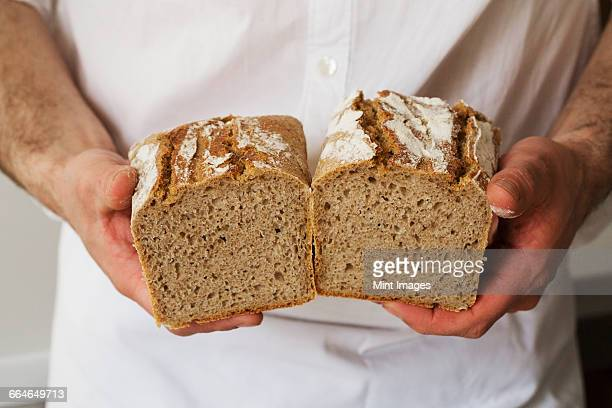 Close up of a baker holding a freshly baked loaf of white bread.