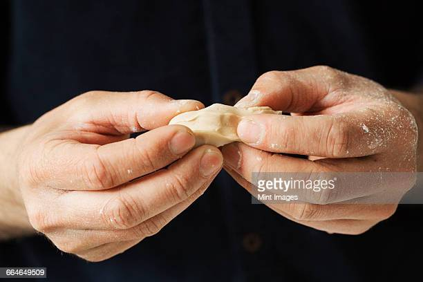 Close up of a baker holding pieces of fresh yeast in his hands.