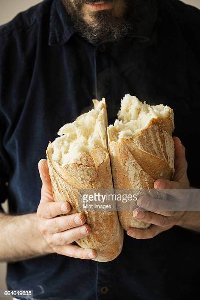 Close up of a baker holding two freshly baked loaves of bread.