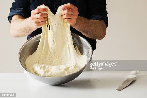 Close up of a baker kneading bread dough in a metal bowl.