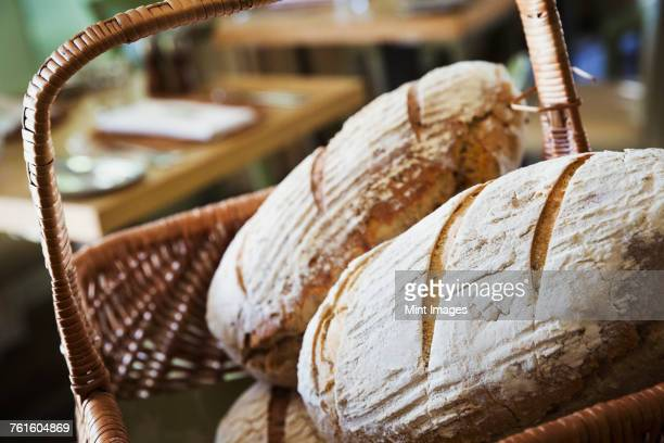 close up of a basket with freshly baked loaves of bread. - artisan stock photos and pictures