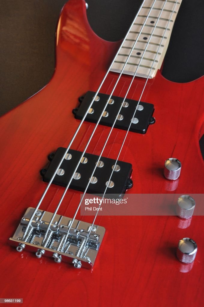 Close up of a bass guitar showing humbucker pickups, bridge, and volume and tone controls, on 25th March 2010 in United Kingdom.
