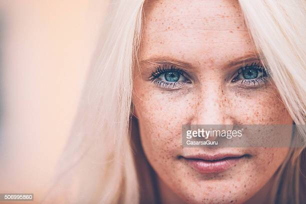 close up of a beautiful blonde woman with freckles outdoors - sproet stockfoto's en -beelden