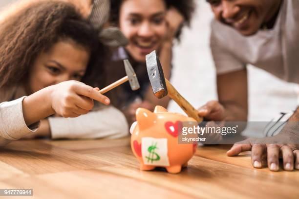Close up of a black family cracking a piggy bank.