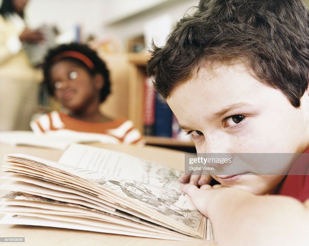 Close Up of a Bored School Boy Sitting at His Desk with an Open Book : Stock Photo