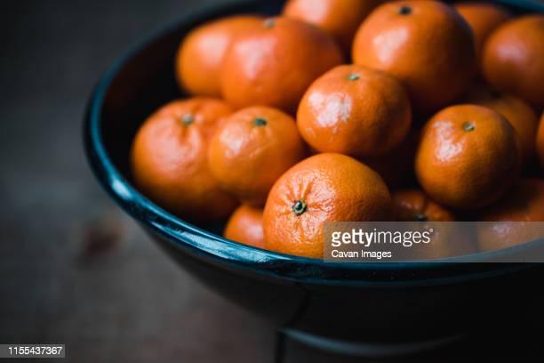 close up of a bowl of fresh mandarin oranges in low light. - ミカン ストックフォトと画像