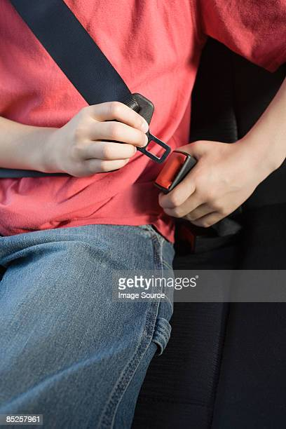 Close up of a boy fastening a seatbelt