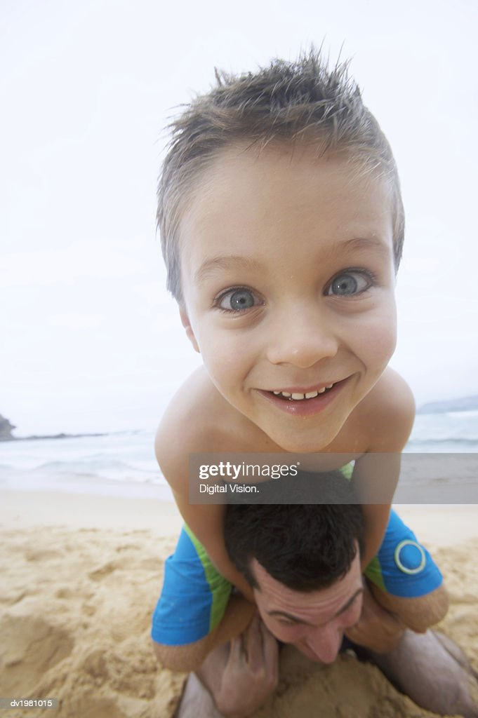 Close up of a Boy on a Beach Carried by His Father : Stock Photo