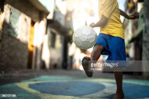 close-up de um garoto jogando futebol na rua - evento de futebol internacional - fotografias e filmes do acervo