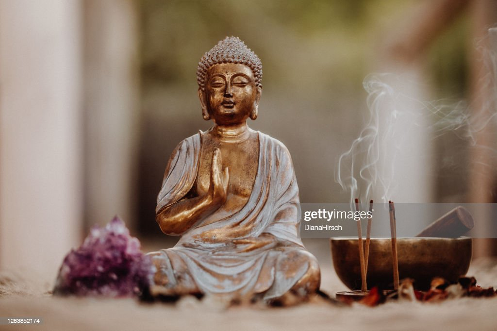 Close up of a Buddha figurine and smoky incense with gong and amethyst : Stock Photo