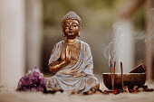 Close up of a Buddha figurine and smoky incense with gong and amethyst