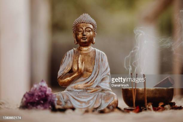 close up of a buddha figurine and smoky incense with gong and amethyst - buddha stock pictures, royalty-free photos & images