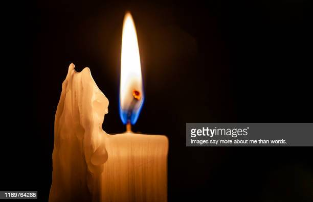 close up of a burning candle against a black background. - religious vigil stock pictures, royalty-free photos & images