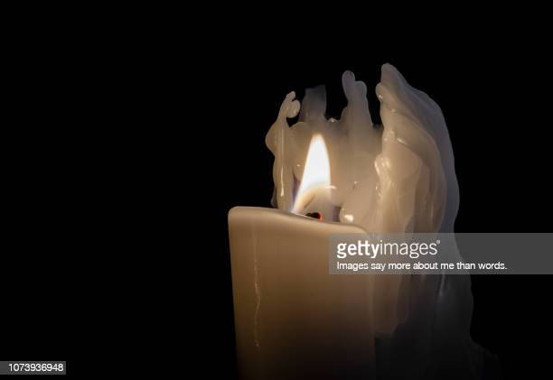 a close up of a burning candle against a dark background. still life. - brazilian waxing stock photos and pictures