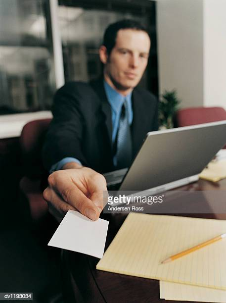 Close up of a Businessman Handing Out His Business Card Sitting at a Table With a Laptop