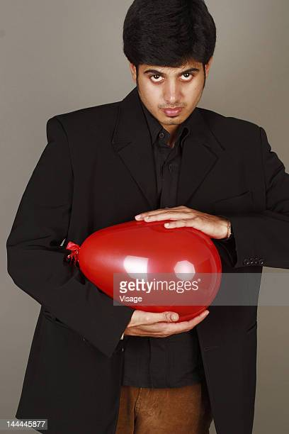 Close up of a businessman holding a balloon