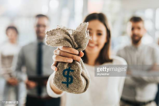 close up of a businesswoman offering money bag. - money bag stock pictures, royalty-free photos & images