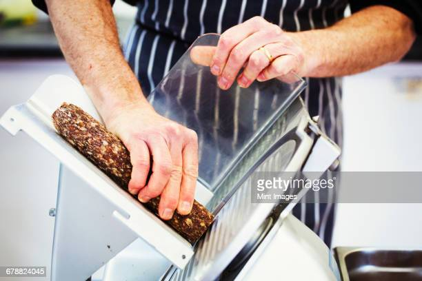 close up of a butcher wearing a striped blue apron, slicing salami with a slicer. - salami stock photos and pictures