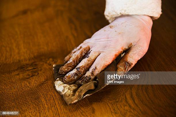Close up of a carpenter wearing protective gloves, applying varnish onto a wooden surface with a cloth.