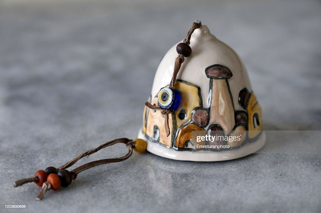 Close up of a ceramic bell on gray table top . : Stock Photo