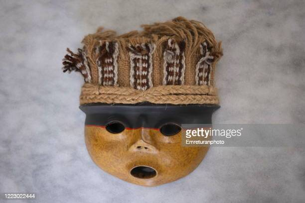 close up of a ceramic south american mask on gray marble tabletop. - emreturanphoto stock pictures, royalty-free photos & images