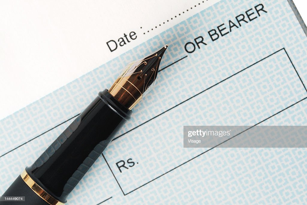 Close up of a cheque and an ink pen : Foto de stock