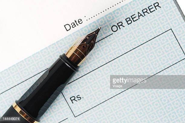 Close up of a cheque and an ink pen