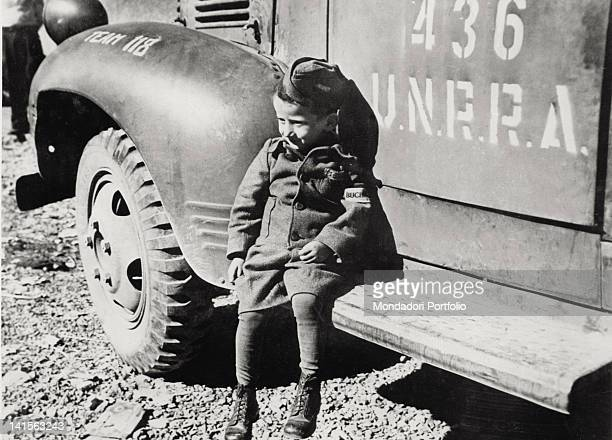 Close up of a child boy who survived the concentration camp in Buchenwald He wears a small uniform and is sat down on the footboard of a lorry of...