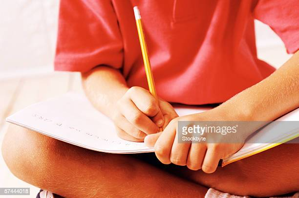 close up of a child's (8-10) hands writing in a notebook