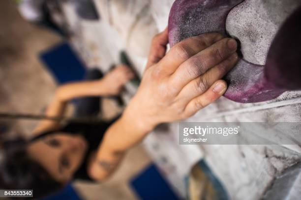 Close up of a climber's hand on a climbing wall in a gym.