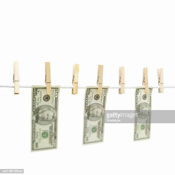 Close up of a clothesline with dollar notes hanging on with clothes pegs
