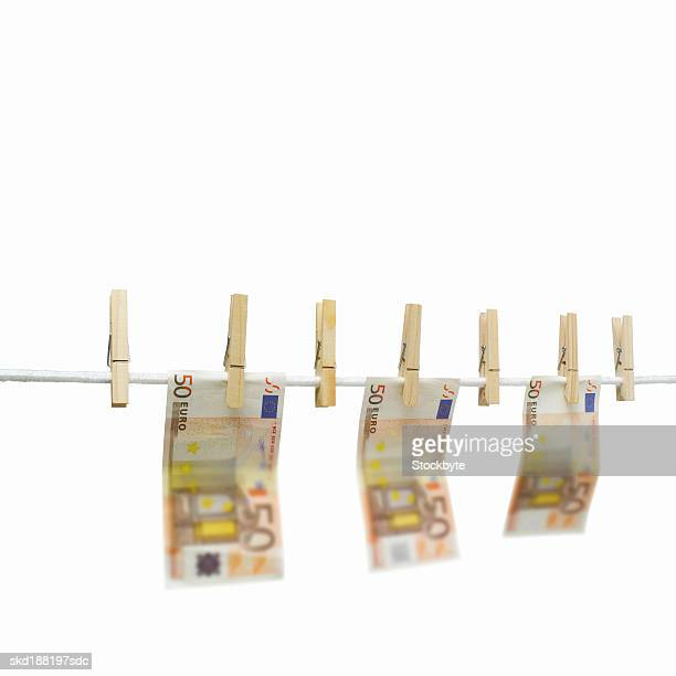 Close up of a clothesline with euro notes hanging on with clothes pegs