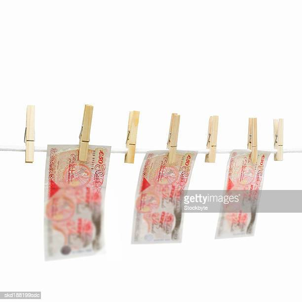 Close up of a clothesline with pound notes hanging on with clothes pegs