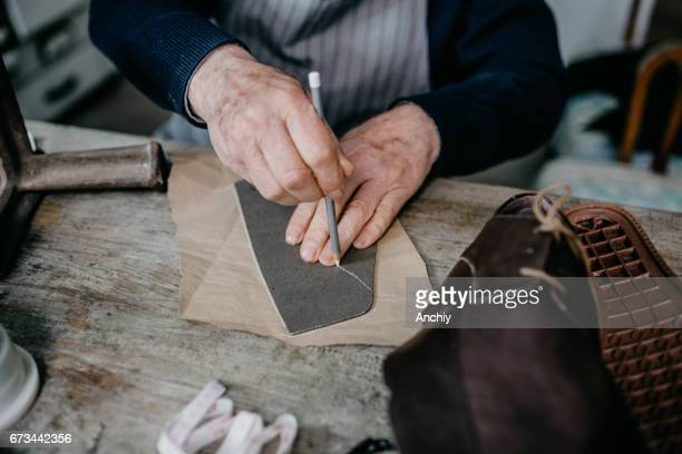 close up of a cobbler working at his shop - calzature di pelle foto e immagini stock