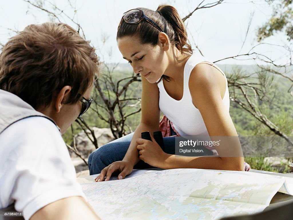 Close up of a Couple Reading a Map on a Car Bonnet : Stock Photo