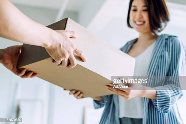 close up of a courier person making a delivery to a customer at home. providing a swift express delivery straight into customer's hands - returning merchandise stock pictures, royalty-free photos & images