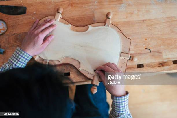 Close up of a craftsman carving the body of a violin from wood